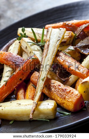 Roasted root vegetables on a black serving platter.  Carrots, parsnips, turnips, red onions, and herbs. - stock photo