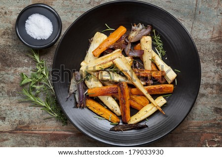 Roasted root vegetables on a black serving platter.  Carrots, parsnips, turnips, red onions, salt, and herbs.  Overhead view. - stock photo