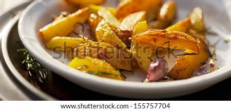 Roasted rosemary garlic potato wedges - stock photo