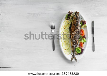 Roasted salmon and vegetables on white plate. - stock photo