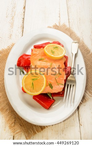 roasted salmon fillet on red paprika, with lemon and rosemary on oval plate - stock photo