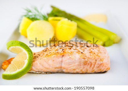 Roasted salmon fillet with green asparagus and potatoes - stock photo
