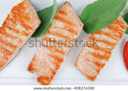 roasted salmon pieces with pepper and lemon on basil leaf over ceramic plate isolated on white background - stock photo