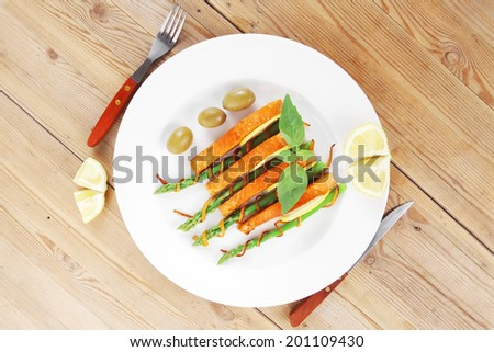 roasted salmon slices with asparagus lemon fried orange peel green olives and cutlery on white plate over wooden table - stock photo