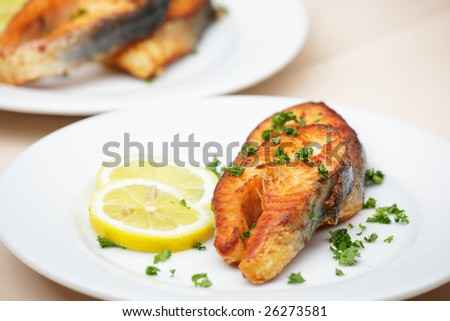 Roasted salmon stakes plated with lemon and parsley