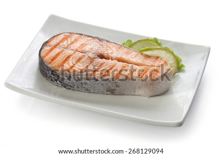 Roasted salmon steak with fresh green lettuce and lime on the white plate