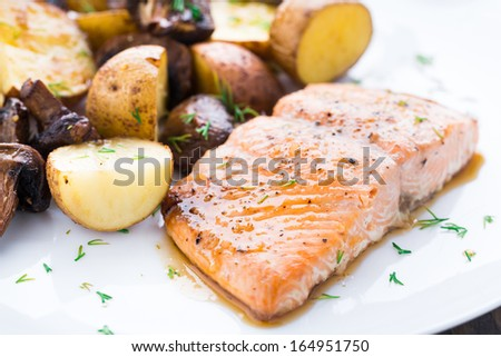 Roasted salmon with potatoes and mushrooms - stock photo