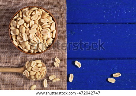 Roasted salted peanuts in bowl and near on blue wooden background, top view