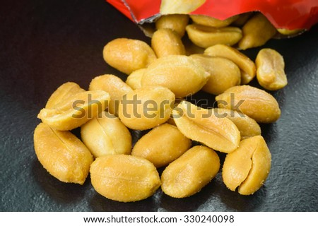 Roasted salted peanuts is a delicate snack but can also be part of a balanced diet. Here is a pile of fresh, roasted tasty peanuts with salt crystals poured out of pack on black stone surface. - stock photo