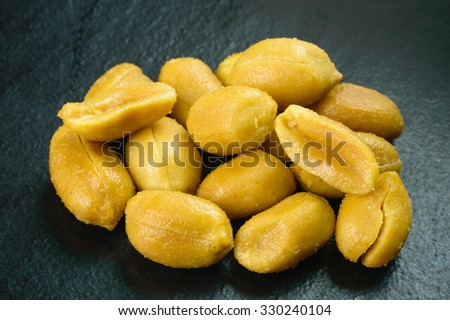 Roasted salted peanuts is a delicate snack but can also be part of a balanced diet. Here is a pile of fresh, roasted tasty peanuts with salt crystals on black stone surface. - stock photo