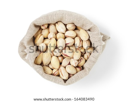 roasted salty pistachios nuts in sack bag from above, isolated on white background - stock photo