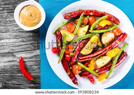 Roasted Sausages, Potatoes, Green Bean, Bell Pepper and Cherry tomatoes drizzled with green spring onion and pieces of chili on a white plate with mustard sauce in a gravy boat, top view - stock photo