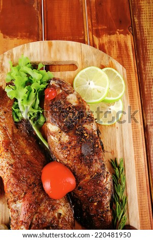 roasted sea fish and castors on wood with tomatoes, lemon and green lettuce salad - stock photo