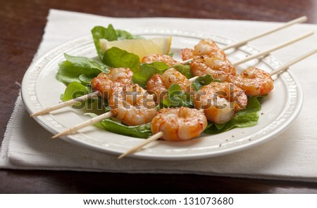 Roasted shrimps on the skewers with lettuce and lemon on the white plate