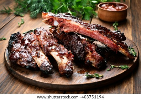 Roasted sliced barbecue pork ribs, focus on sliced meat - stock photo