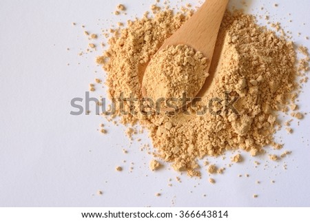 roasted soybean flour wiht wood spoon on white background