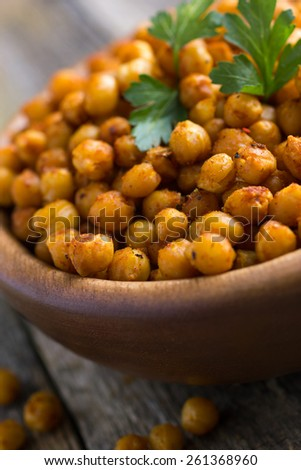Roasted  spicy chickpeas on rustic background, close up, selective focus - stock photo