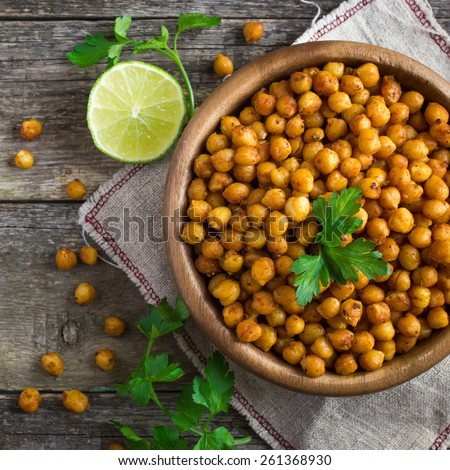 Roasted  spicy chickpeas on rustic background, top view, square image - stock photo