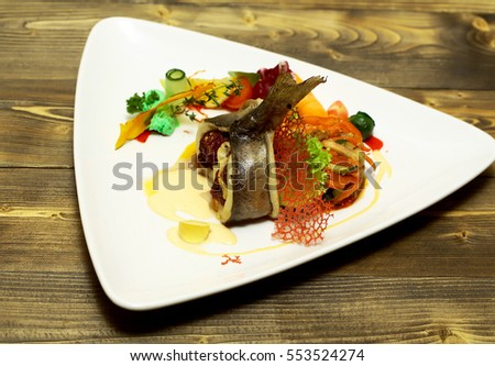 Roasted stuffed fish served with vegetables, red tomato, orange carrot, green salad, yellow lemon and sauce on plate on wooden background. Modern molecular gastronomy