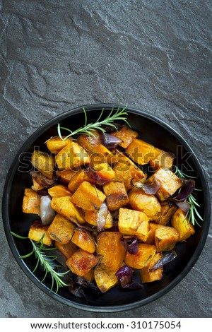 Roasted sweet potato with red onion and rosemary.  Black dish, overhead view, over dark slate. - stock photo