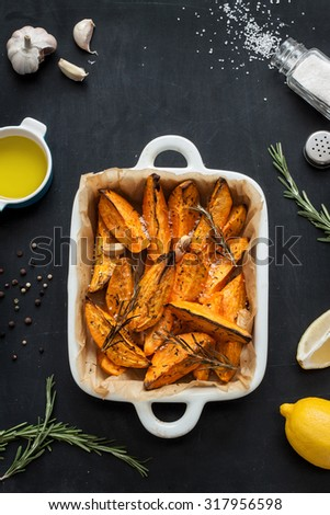 Roasted sweet potatoes in white ceramic dish. Olive oil, lemon, salt, pepper, garlic and rosemary around. Black chalkboard as background. Kitchen worktop scenery from above. - stock photo