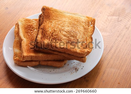 Roasted toast bread on wooden table - stock photo