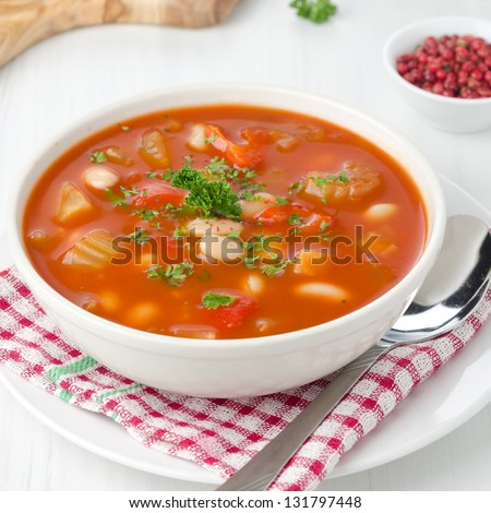 roasted tomato soup with beans, celery and sweet pepper garnished with fresh parsley closeup - stock photo