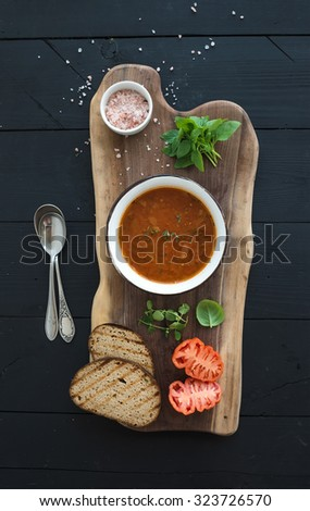 Roasted tomato soup with fresh basil, spices and bread in vintage metal bowl on wooden board over black background, top view - stock photo