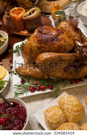 Roasted turkey garnished with cranberries on a rustic style table decoraded with pumpkins, gourds, asparagus, brussel sprouts, baked vegetables, pie, flowers, and candles. - stock photo