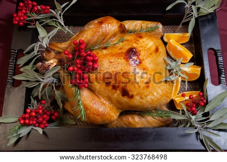 Roasted turkey garnished with sage, rosemary, and red berries in a tray prepared for Christmas dinner. Holiday table, candles and Christmas tree with ornaments.