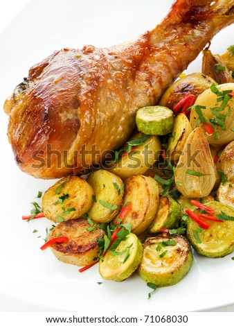 Roasted turkey leg with vegetables. Shallow dof. - stock photo