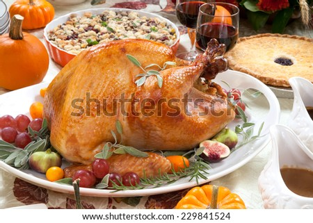 Roasted turkey on a server tray garnished with fresh figs, grape, kumquat, and herbs on fall harvest table. Red wine, side dishes, pie, and gravy. Decoraded with mini pumpkins, candels, and flowers.