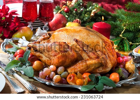 Roasted turkey on holiday table, candles and Christmas tree with ornaments - stock photo