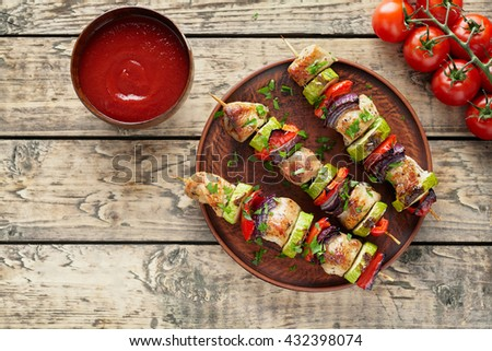 Roasted turkey or chicken meat shish kebab skewers with ketchup sauce, chopped parsley and tomatoes on rustic wooden table background. Traditional barbecue grill food - stock photo