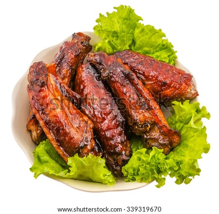roasted turkey wings garnished with fresh green salad on the plate on white background  - stock photo