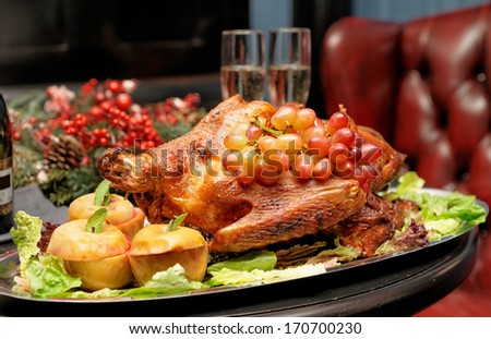 Roasted turkey with baked apples and grapes, festive dish - stock photo