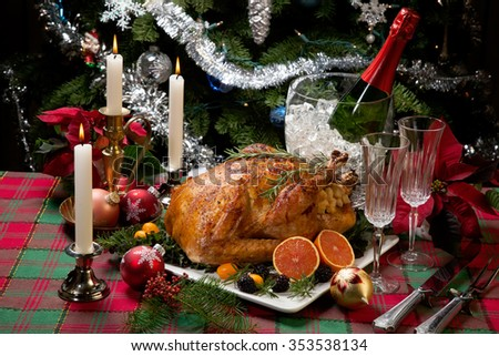 Roasted turkey with fresh fruits, flutes of champagne, Christmas tree, candles, and decorations