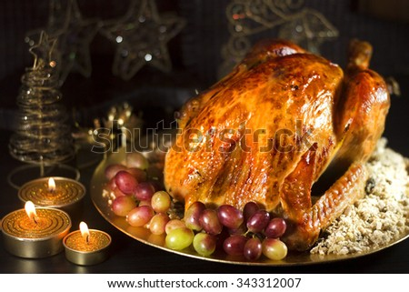 Roasted turkey with grapes and brazilian food farofa on dark background with candles.