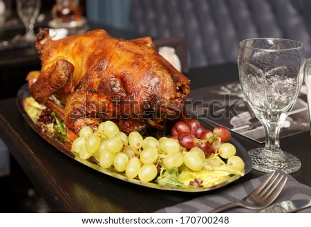 Roasted turkey with grapes on a restaurant table - stock photo