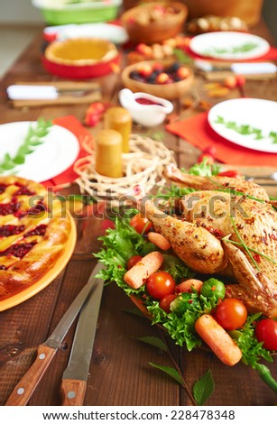 Roasted turkey with spices and vegetables and other festive food on served table - stock photo