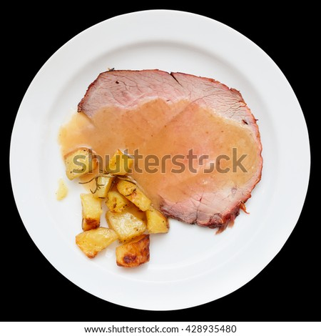Roasted veal fillet with fried potatoes, isolated on black background - stock photo