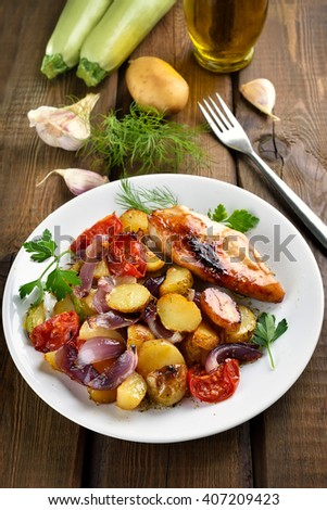 Roasted vegetables and chicken breast on wooden background