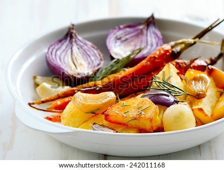 Roasted vegetables in a white plate. Vegetarian dish. - stock photo