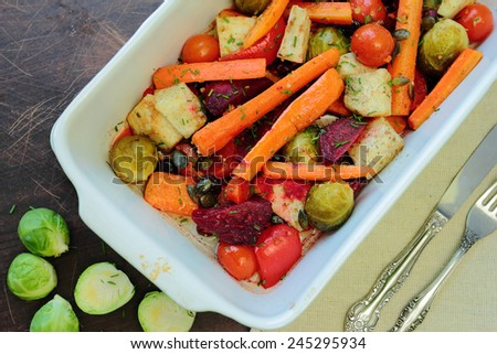 Roasted vegetables in oven with cutlery - stock photo