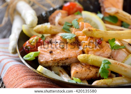 Roasted  white asparagus with fried salmon served in an iron frying pan - stock photo