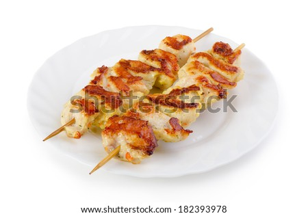Roasted white meat skewers on plate - isolated on white - stock photo