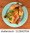 Roasted whole chicken on a blue plate on wooden background - stock photo