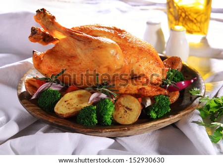 Roasted whole chicken on a plate with vegetables