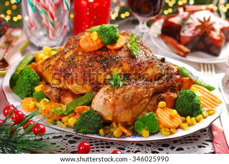 roasted whole chicken with  broccoli,carrot,corn and green peas on christmas table