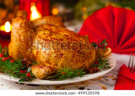 Roasted whole chicken with Christmas decoration. Wooden background. Front view.
